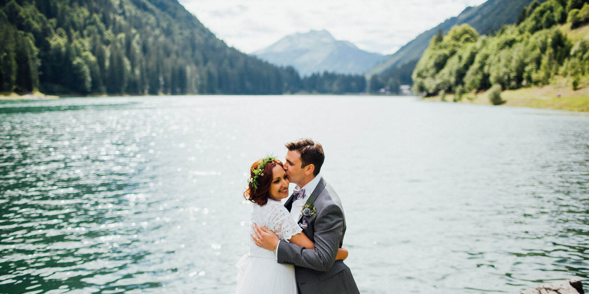 bride and groom kissing on their lake side wedding in the alps
