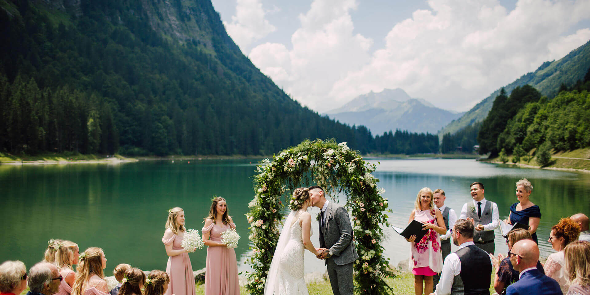 bride and groom kissing on their alpine lake wedding in montriond