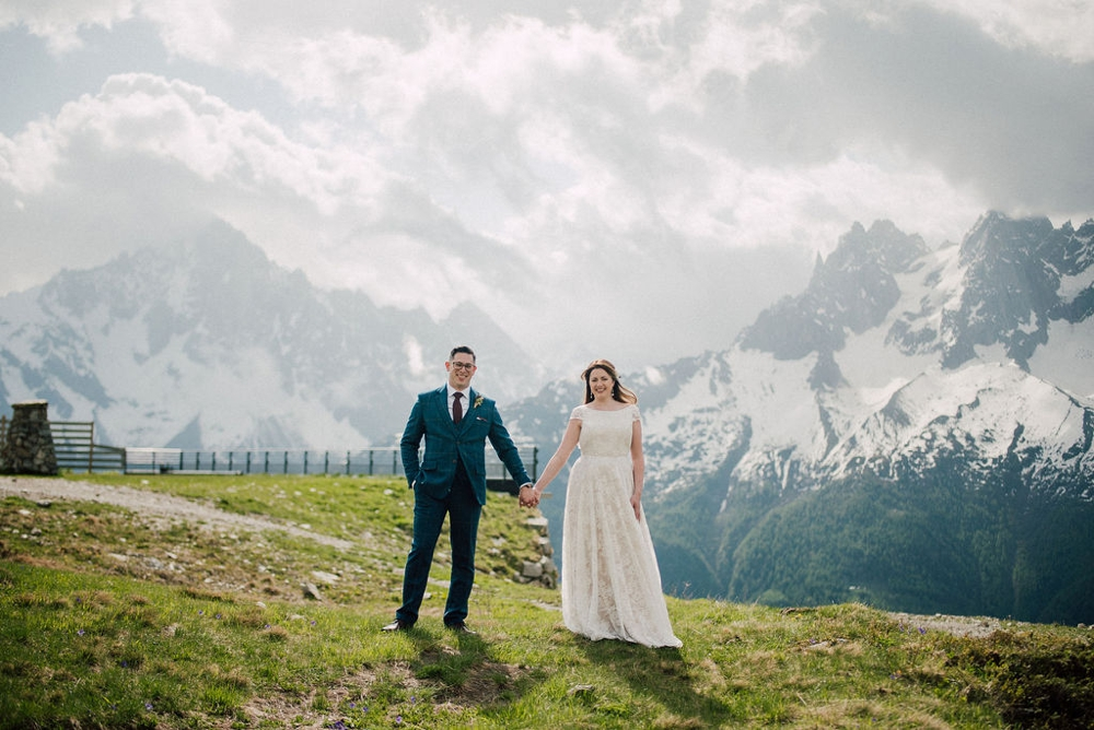 couple at the top of a mountain celebrating their elopement facing the mont blanc in the french alps